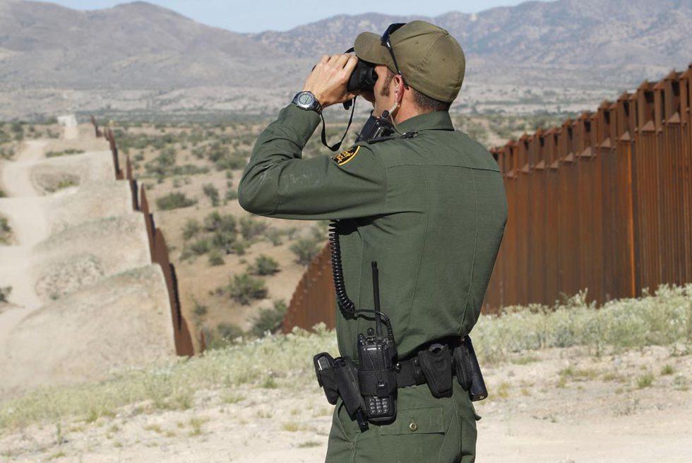 Un agente de la patrulla fronteriza vigila la valla en Nogales