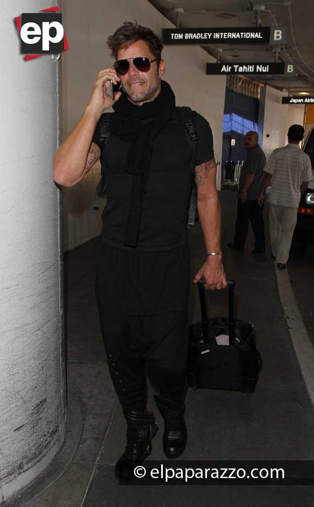 Con su maleta avanzo rápidamente el famoso cantante por la terminal internacional del aeropuerto de Los Angeles, CA.