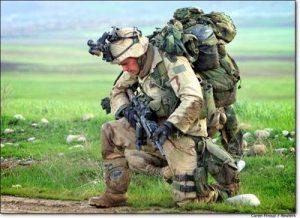 Солдаттын блог сүрөттүн бардык жабдууларды көтөрүп тизелеп