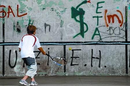 Un niño juega en un frontón de Arrasate (Guipúzcoa) lleno de pintadas alusivas a ETA, ayer.