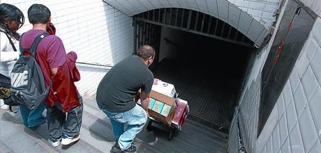 Un hombre cargado con cajas desciende penosamente por las escaleras del metro de Arc de Triomf.