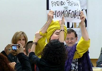 El 'drag queen' Shangay Lilly muestra una pancarta en la que califica de homófobo al PP ante la presencia de Mariano Rajoy, hoy en Madrid.