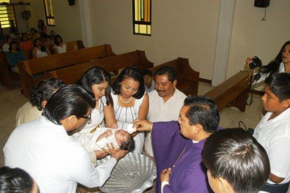 Ángel Estrella bautiza al pequeño Arturo Nerhack Alonso Can en la iglesia del Seminario Menor.