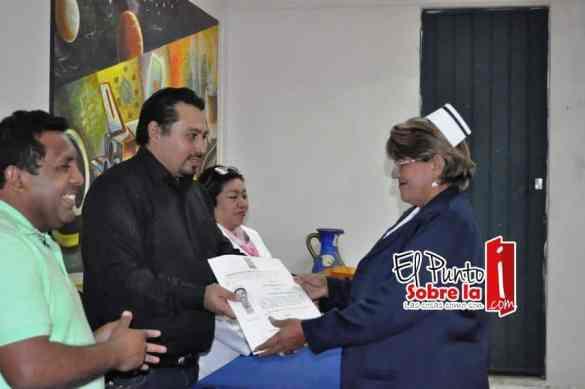 Claribel Bobadilla Castro recibe de Luis Alain Matos de la Asociación de Profesionistas de Quintana Roo su título como licenciada en Enfermería.