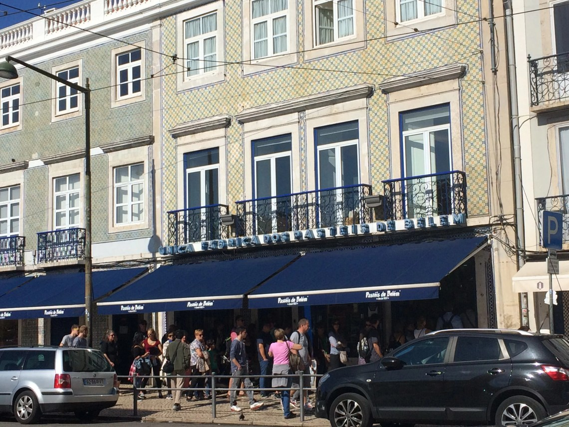 Fábrica de Pastéis de Belém, shop exterior. A 3 storey building with checkered tiles in blue and yellow. A blue canopy covers the shop front on the ground floor with crowds of people queuing.