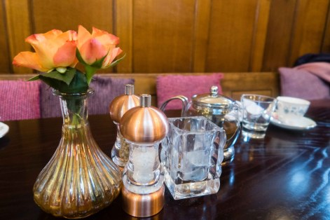 Table setting with flowers on the left, salt and pepper mill and candle