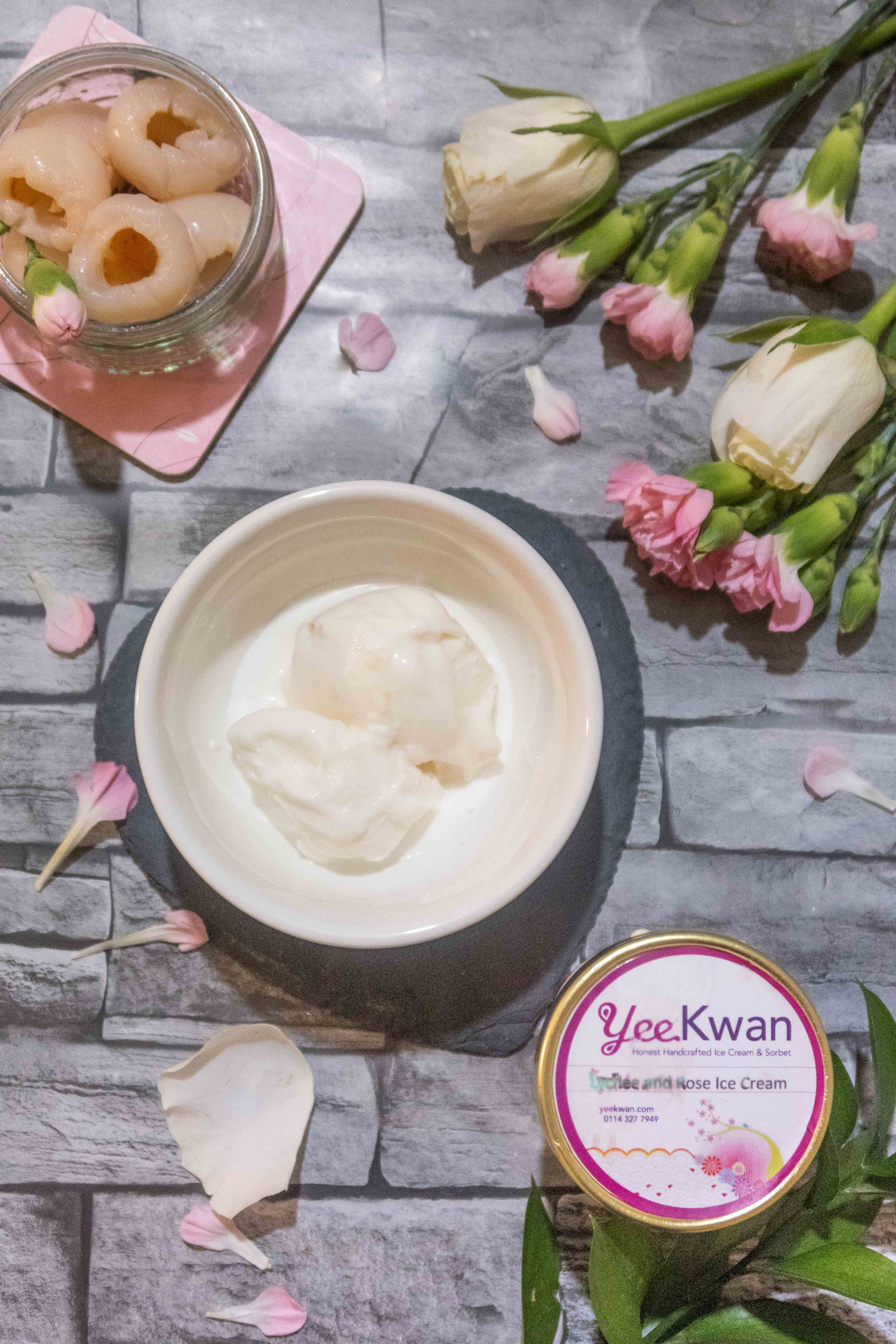 Yee Kwan's Lychee and Rose ice cream, in the tub and in a bowl, set against a background with roses and lychees in a ramekin