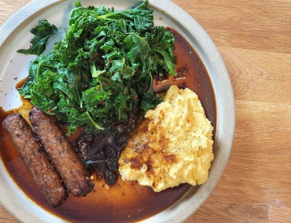 A plate with kale, root veg mash, vegetarian sausages and veggie gravy