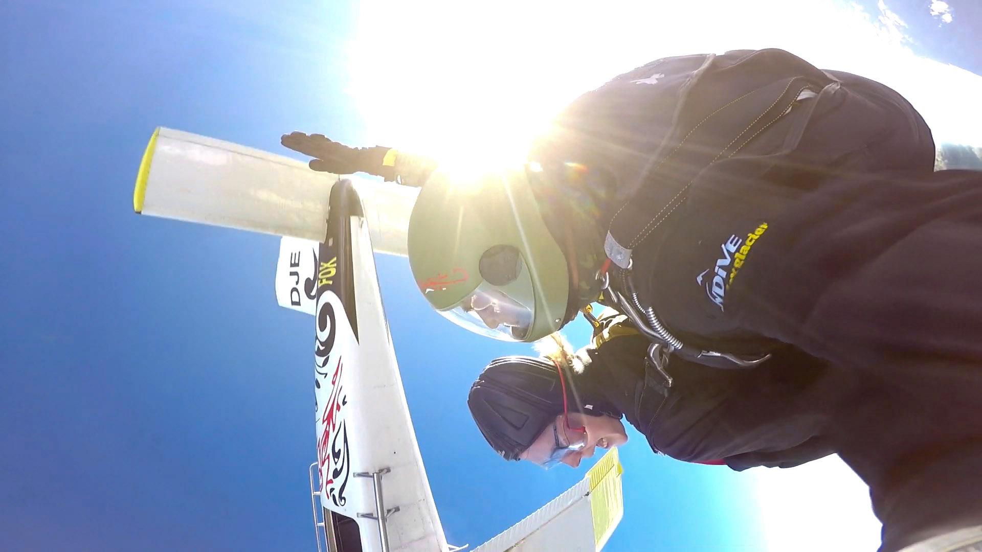 Skydive net uit het vliegtuig, we maken een rol in de lucht en het vliegtuig zien we op de achtergrond