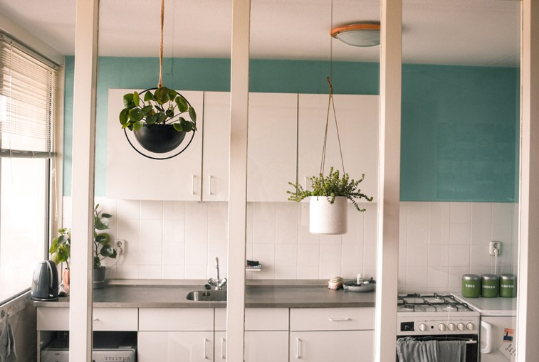Hangbloempotten voor een raam tussen de woonkamer en de keuken