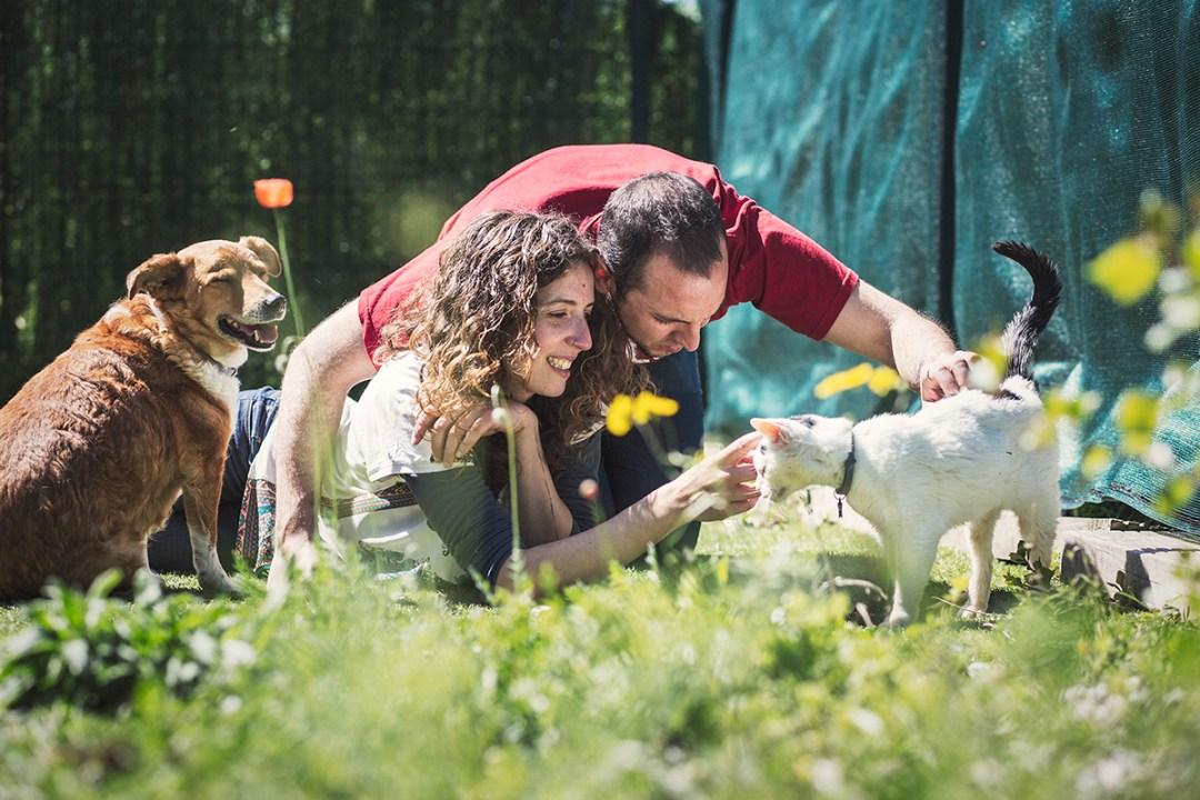 pareja en el jardín con su gato y perro