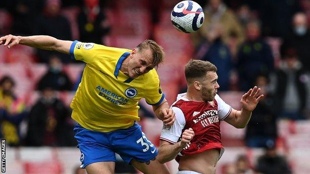 Brighton's Dan Burn and Arsenal's Calum Chambers attempt to head the ball