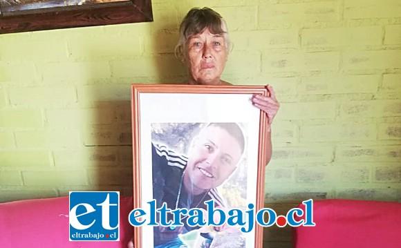 Acá vemos a Fresia Soto sosteniendo entre sus brazos un cuadro con la foto de su hijo.