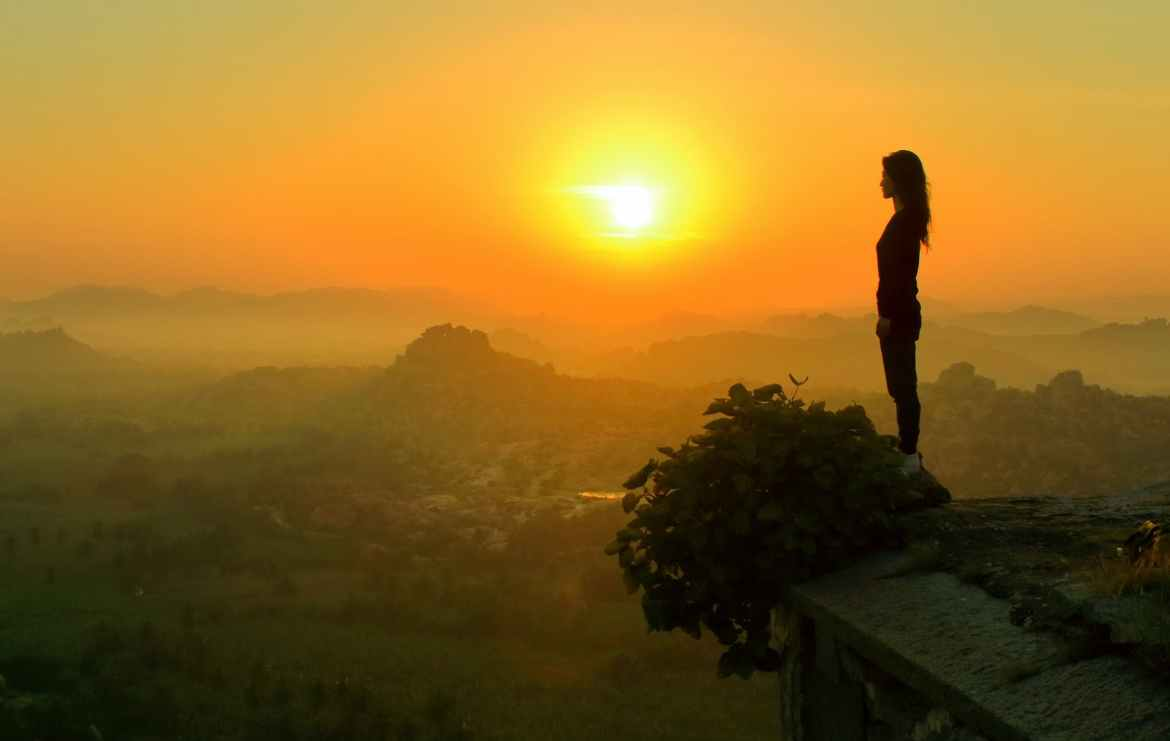 silhouette of woman standing near cliff