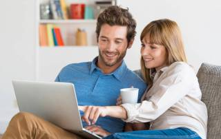 Couple on Couch looking at homes online