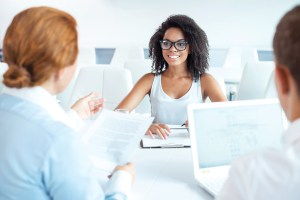 Young African beautiful woman having an interview or business meeting with employers. Employers examining her CV and using laptop. White modern office interior
