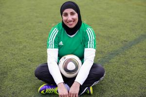Shireen Ahmed sitting with soccer ball in lap, wearing hijab