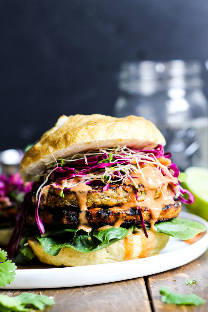 These vegan Asian Veggie Burgers are full of flavor & plant protein! Perfect for weekend grilling, topped with Mango Cabbage slaw and spicy Sriracha sauce.