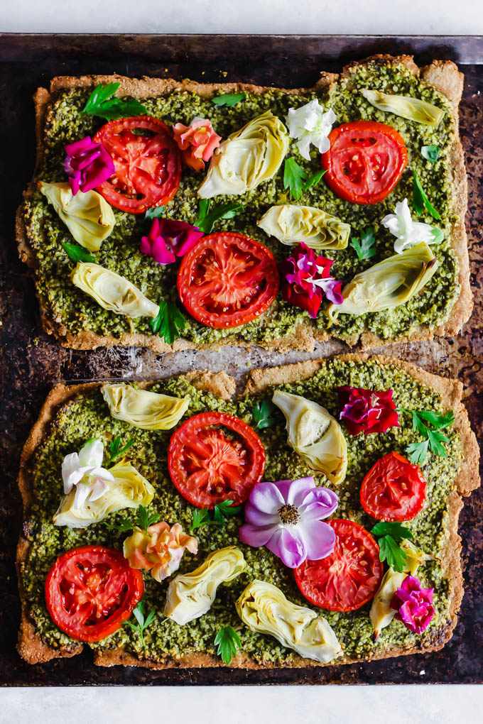 Impress your dinner party guests with this beautiful Floral Tomato & Artichoke Pesto Flatbread! This appetizer only requires 30 minutes to make & is full of flavor. (vegan)