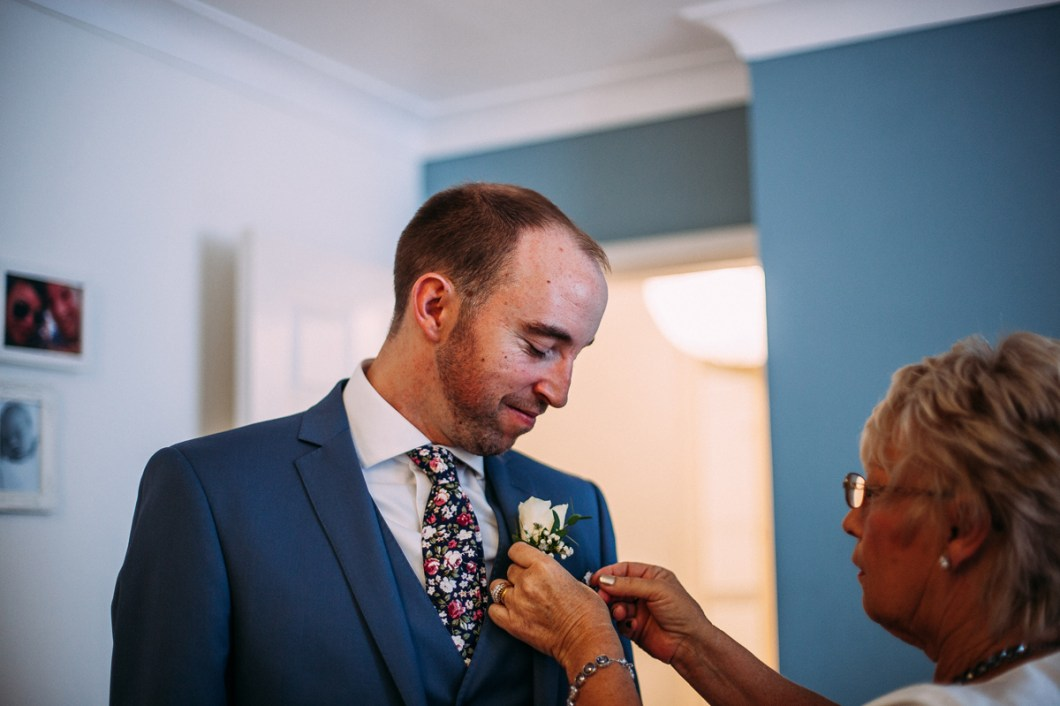 Groom wearing a floral tie and buttonhole