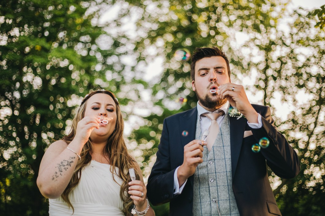 Bride and groom blow bubbles