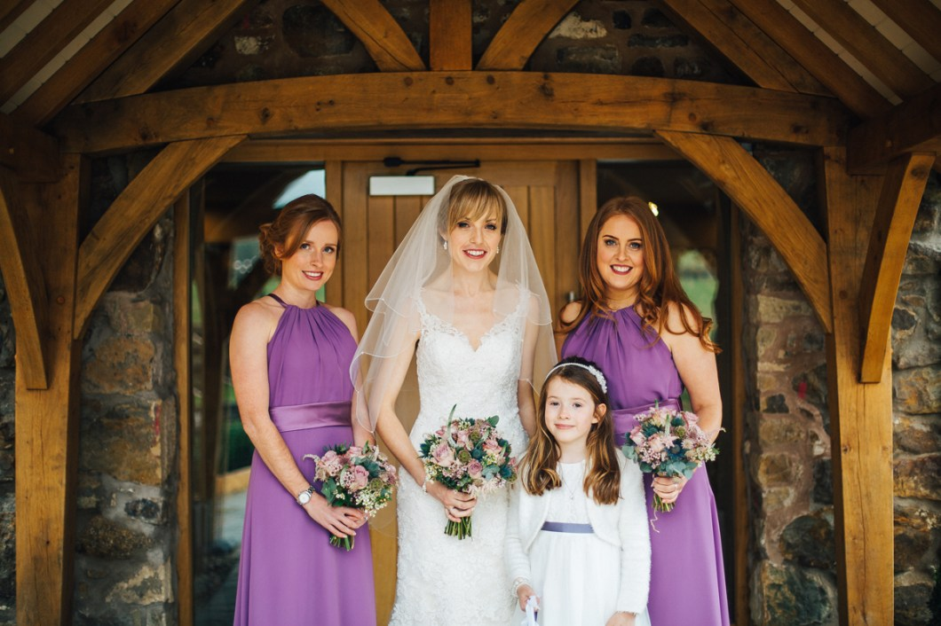 Bride and bridesmaids wearing purple dresses