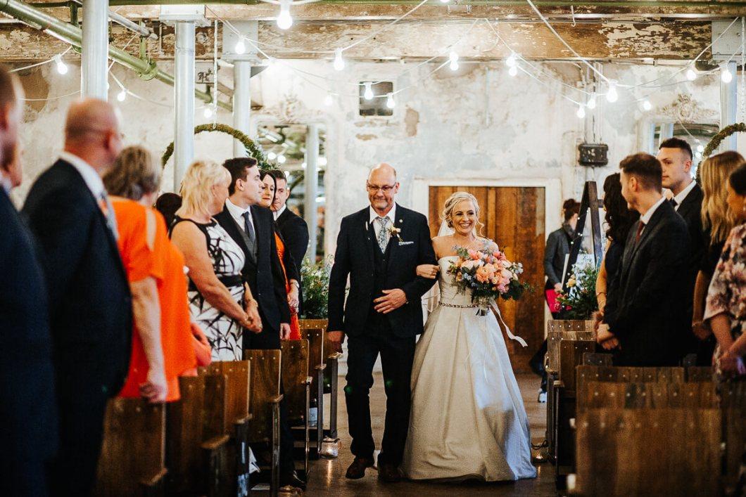 Bride walking down the aisle in a Lulu Brown's dress