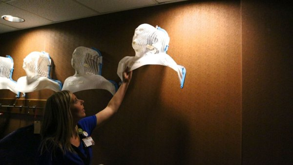 A radiation therapist takes down a mask from the wall. It will be snapped down over a cancer patient's head. That's serious stuff, right? Photo by Emily Siner