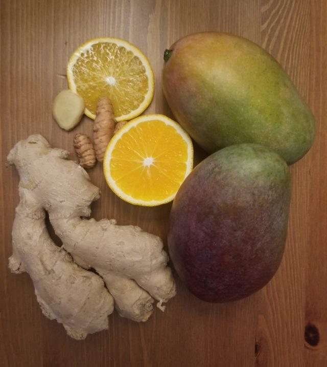 garlic, turmeric, ginger, oranges, and mangoes on a table