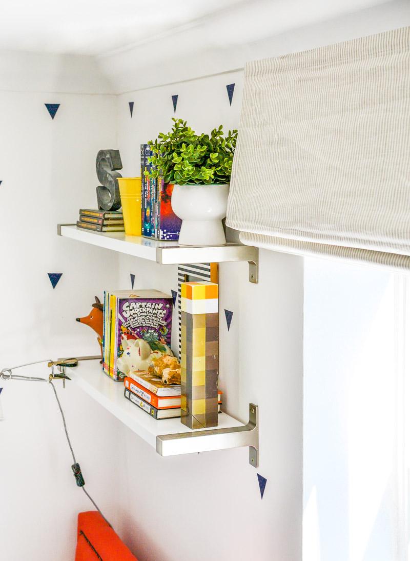Grey linen stripe roman blinds in boys room - detail with shelves