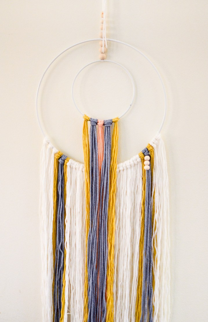 Attaching first set of wooden beads to DIY wall hanging