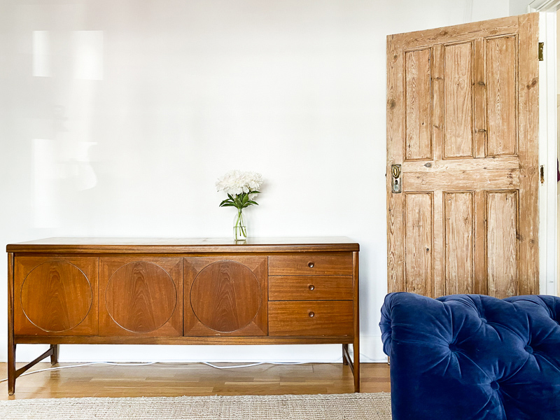 Peonies on mid-century console against Wevet Farrow and Ball