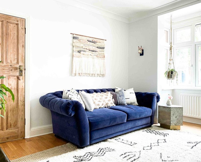 Eclectic living room makeover with navy Chesterfield sofa bed and Beni Ourain rug