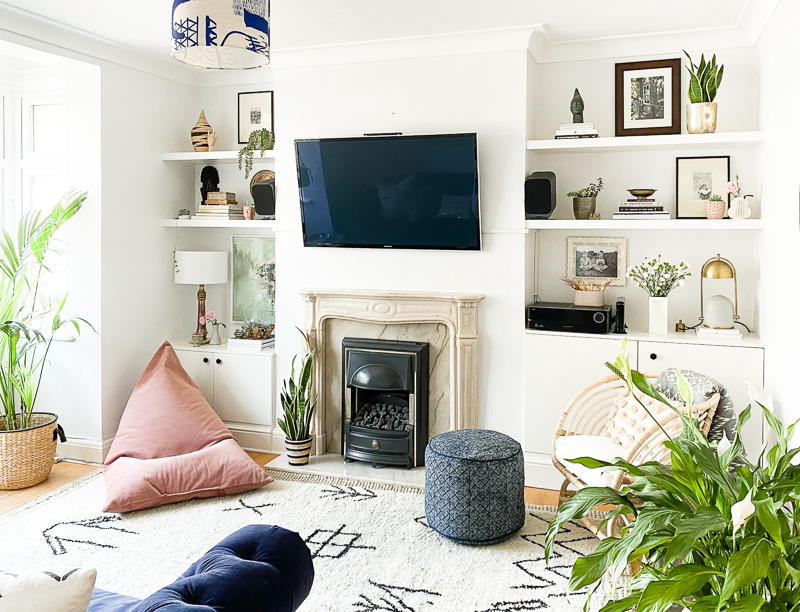 TV hung over fireplace in living room with built in shalves