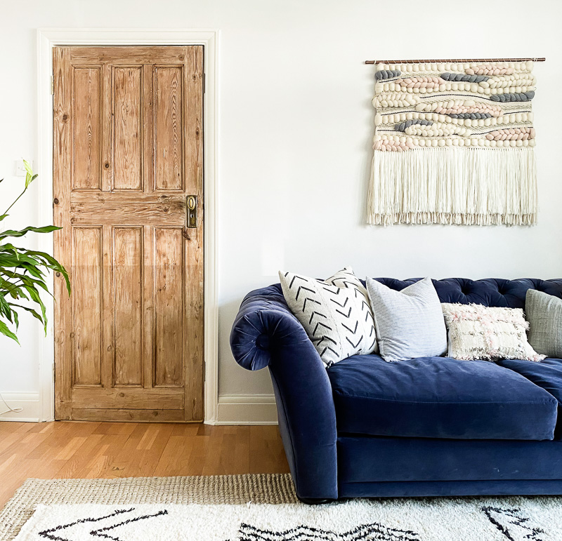 Bare wood door in Edwardian living room with navy chesterfield & woven wall hanging