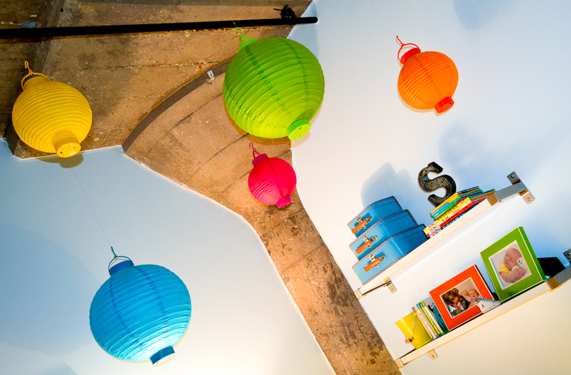 Paper lanterns in toddler bedroom in industrial loft with concrete ceilings