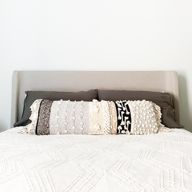 West Elm white bedding and Anthropologie All Roads Yucca cushion