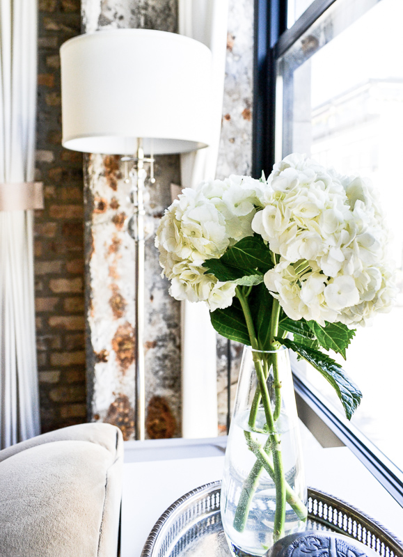 Hydrangeas on sofa table with exposed brick wall