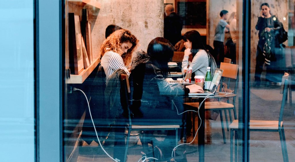Women collaborating around a table at a coffee shop.