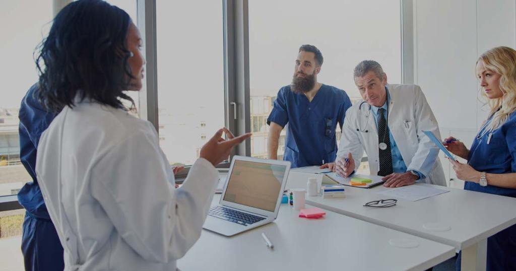 Physicians meet around a table.