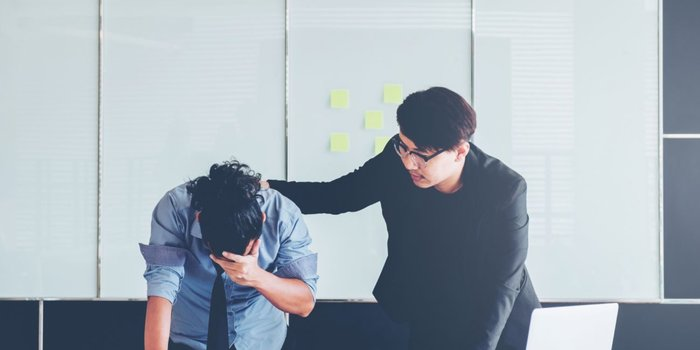 This is an image of two men in an office. The one on the left is bent over a desk crying and the one on the right has his right hand on his shoulder.
