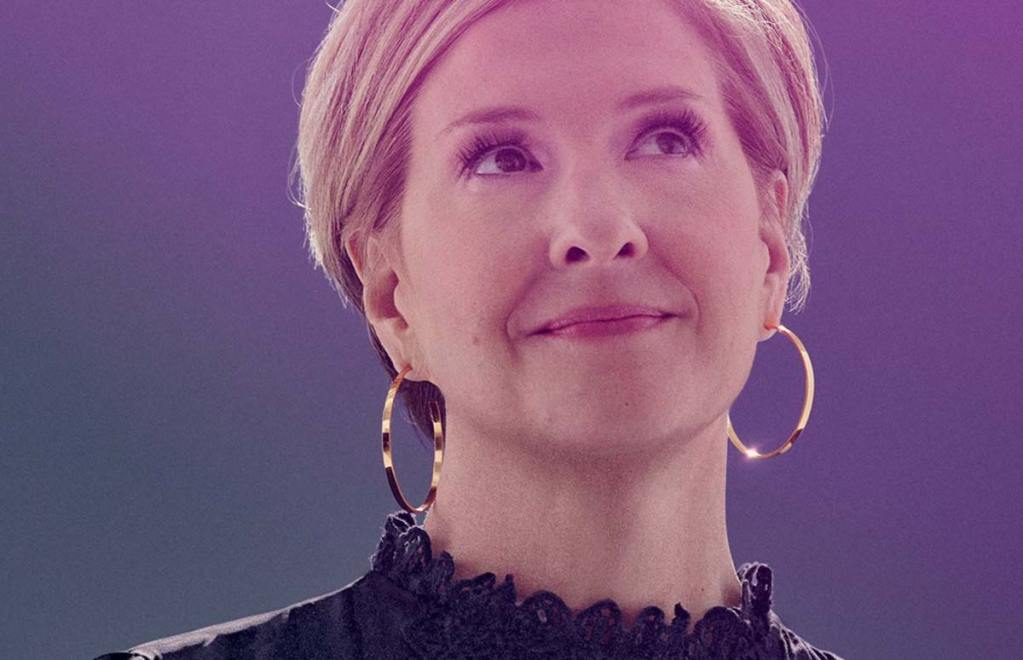 Brene Brown smiles on stage will delivering the wisdom.
