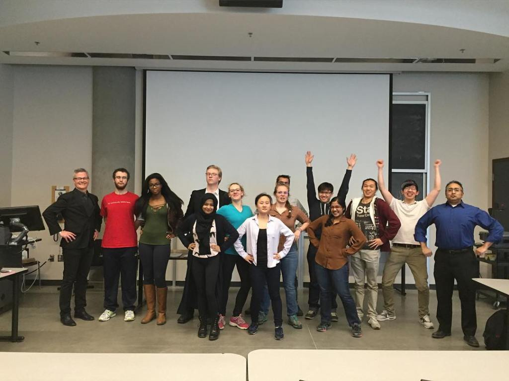 A ground of people standing in power poses. Some have hands on hips and others have their arms in the air. All are in a classroom and smiling at the camera.