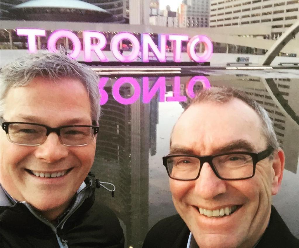 """A close up of two men's faces. Both are smiling widely, and both have grey hair and black framed glasses. There is water behind them with large neon pink letters on the other side that say """"TORONTO."""""""
