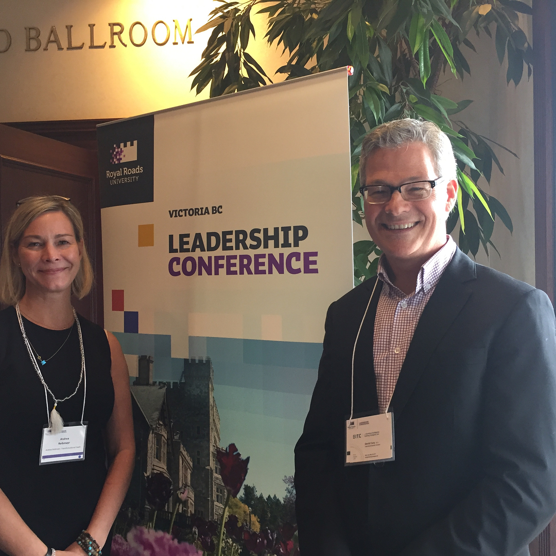 "A woman on the left and a man on the right both wearing black are indoors and smiling. Gold letters above a door behind them say ""ballroom."" Direction behind them is a backdrop that says ""Leadership Conference"" in black and purple letters."