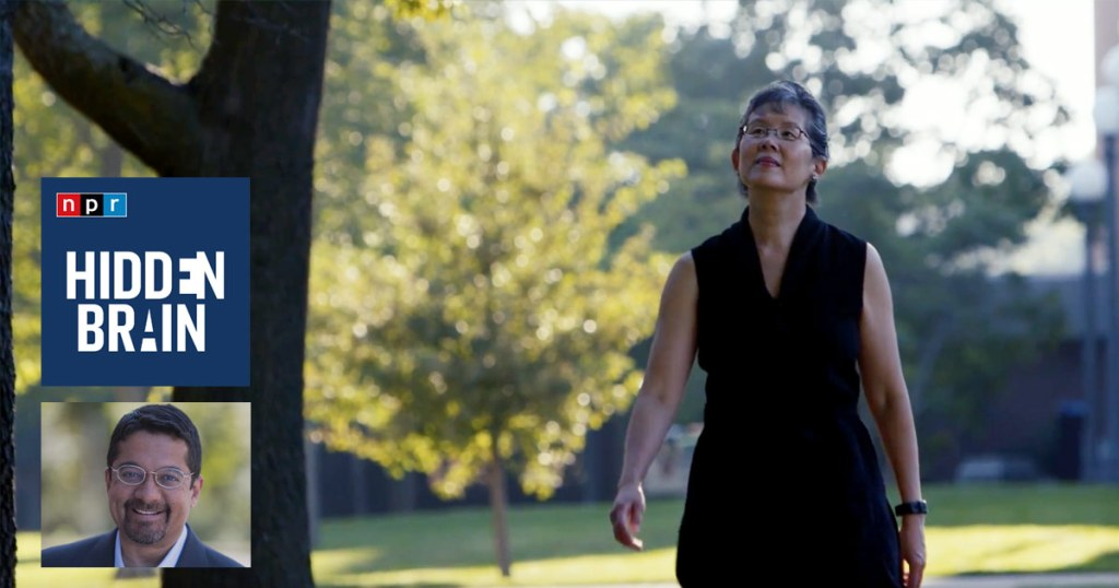 Ming Kuo walks under the trees on campus: NPR Hidden Brain.