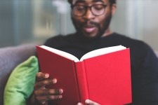 A Black man sits on a sofa reading a book with a red cover. The book is in focus in the foreground, while the man is slightly out of focus. He has black framed glasses and a beard.