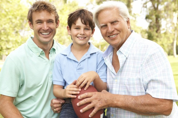 Grandfather With Father And Son Playing American Football Togeth