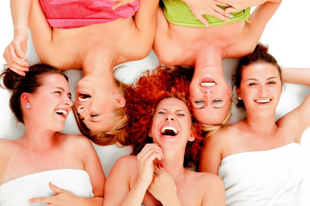 A picture of five girl friends having fun in spa over white background