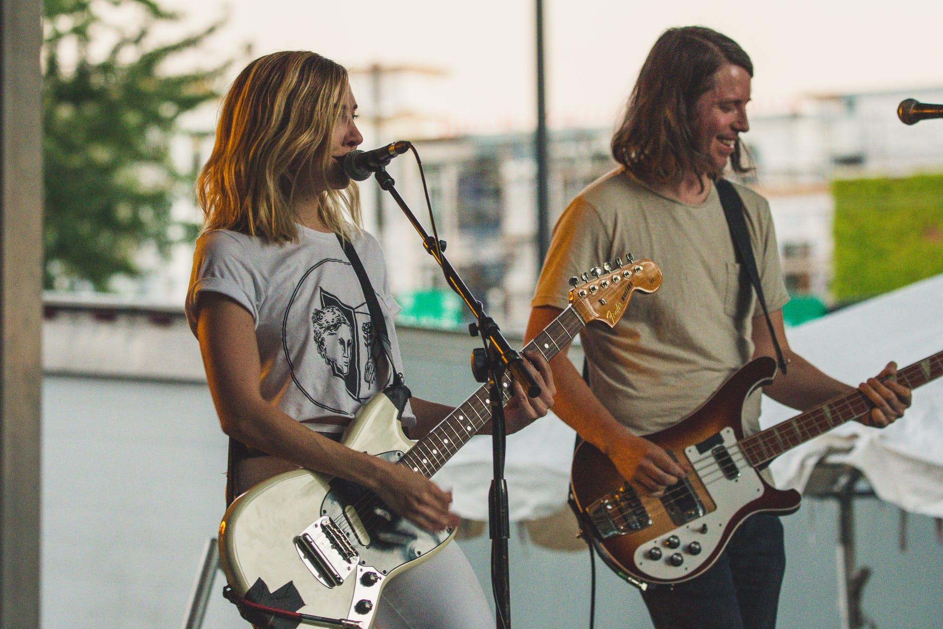 woman playing guitar while singing beside man playing bass guitar near microphone